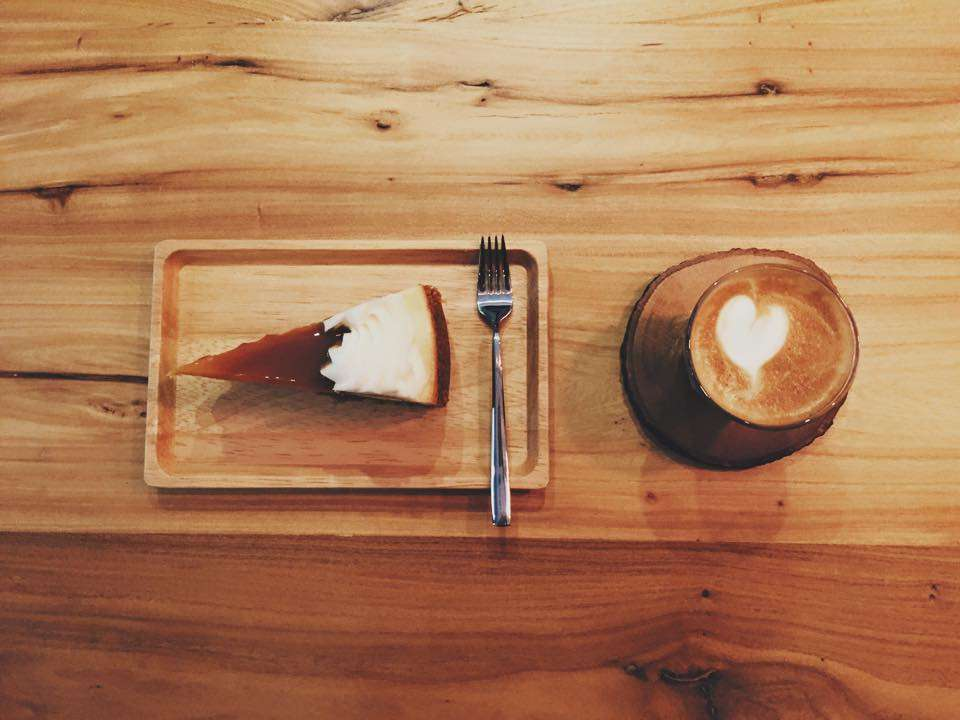 A piece of cheesecake and a cappuccino on a wooden table.