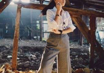 A young woman poses in brown slacks