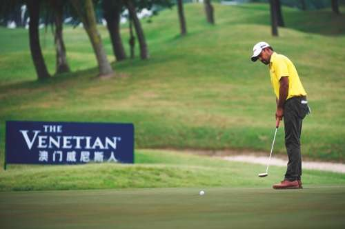 A man wearing a yellow t-shirt and olive green trousers and white hat plays golf in Macau.