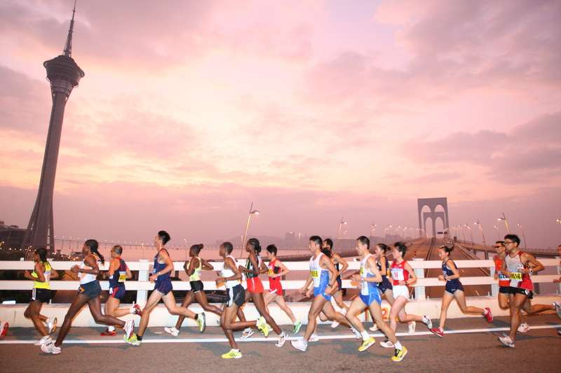 Runners running over bridge in Macau marathon