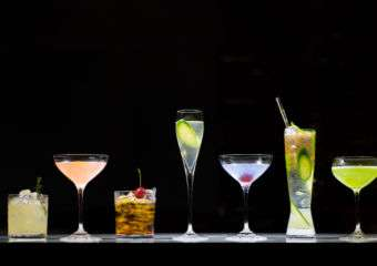 Five different cocktails displayed on a counter against black background.