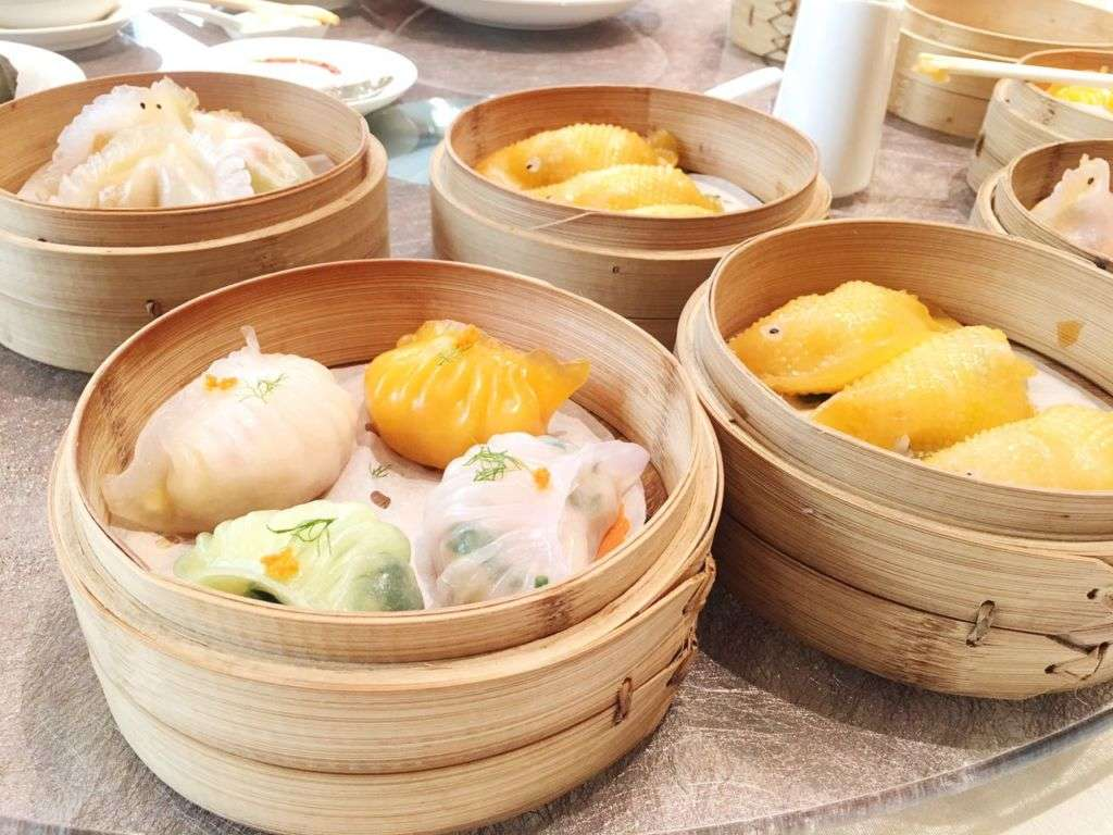 Four wooden baskets holding different dim sum