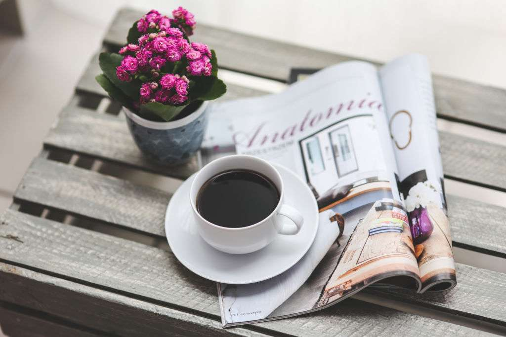 Cup of coffee on magazine and flowers