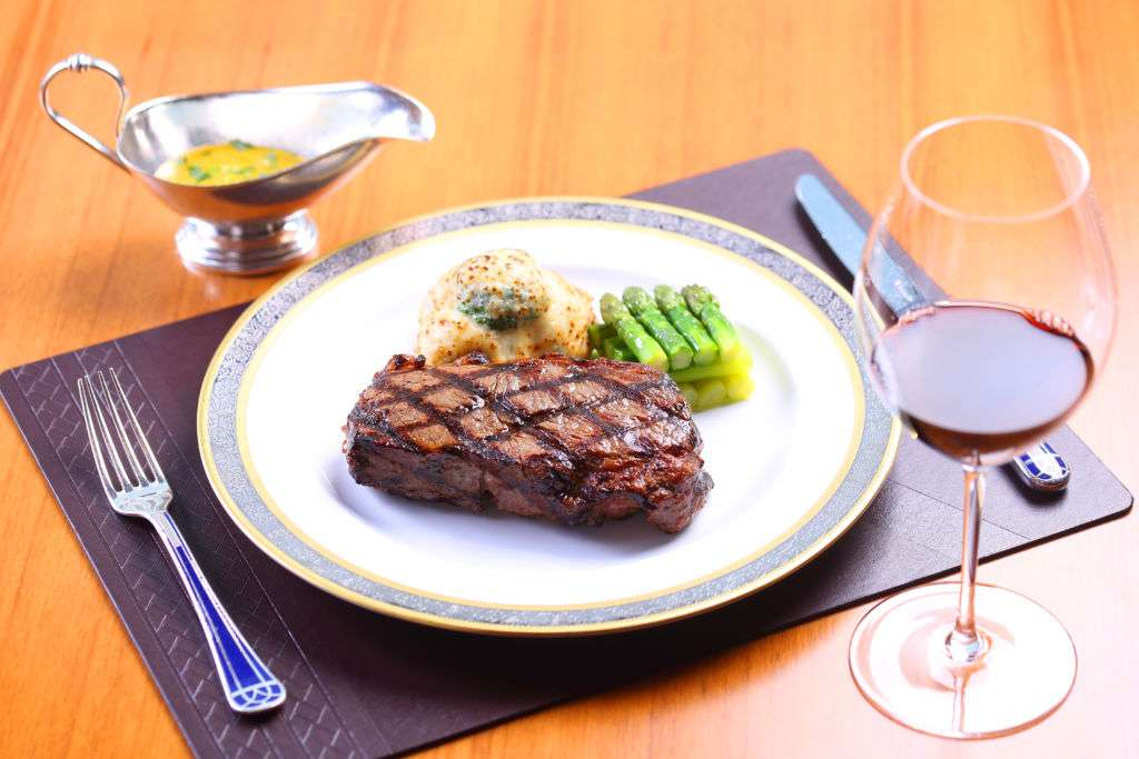 Steak with puree and asparagus on a plate mat, glass of red wine and gravy boat on a wooden table