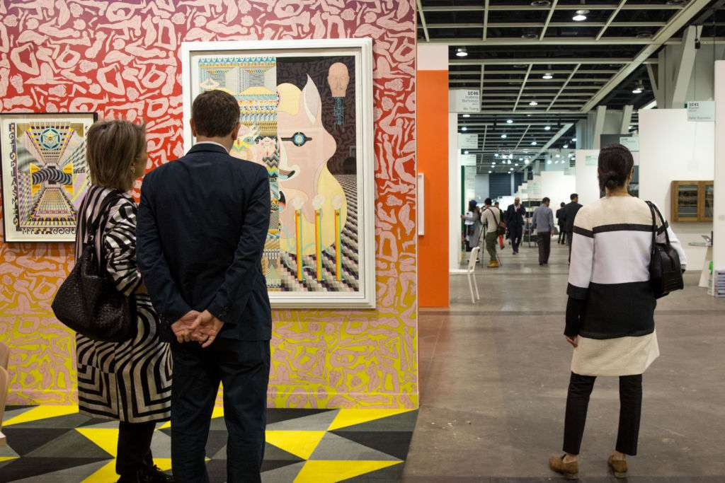 A man and woman look at a painting at Art Basel art show in Hong Kong.