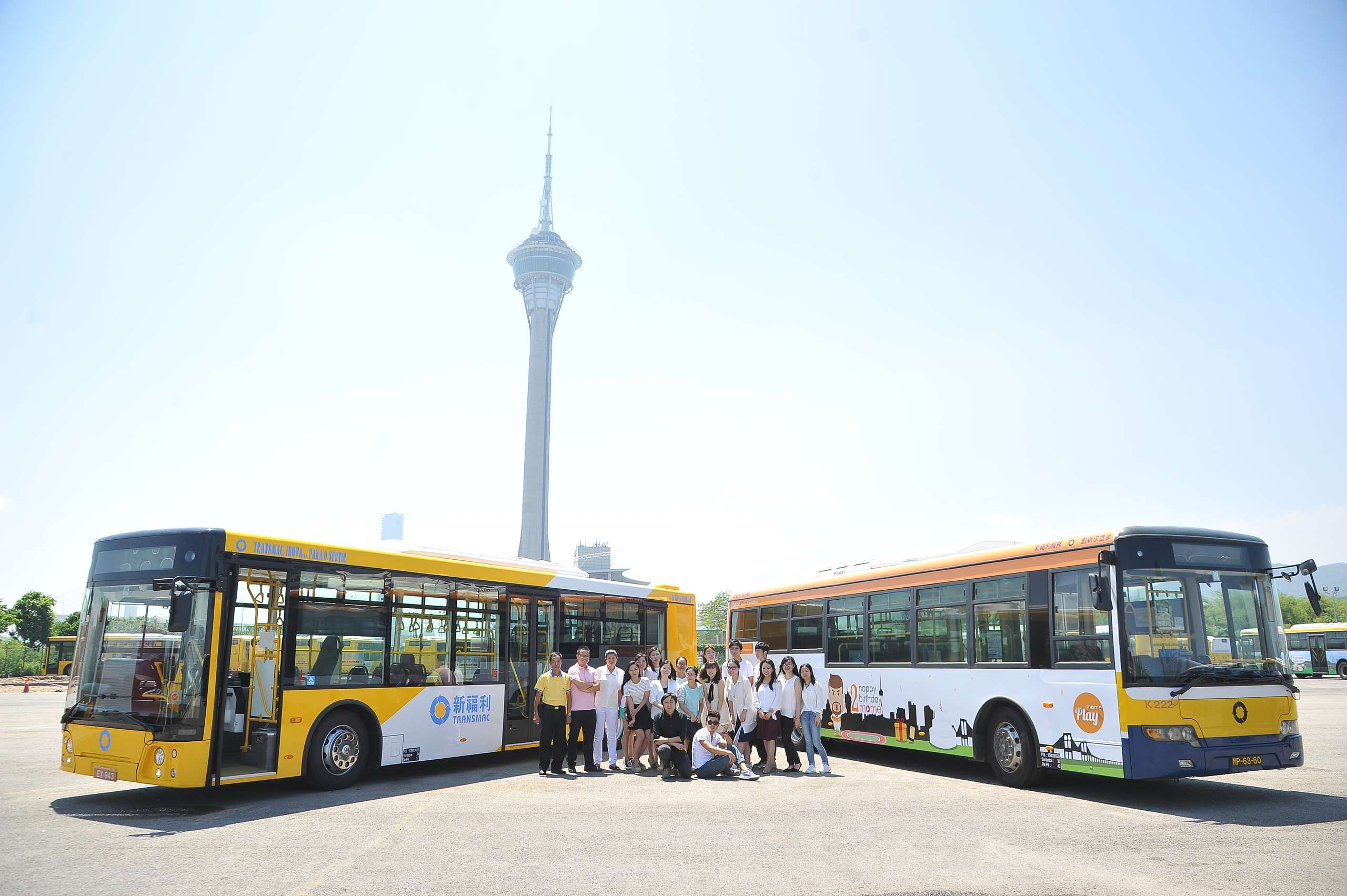 Group photo in front of two buses with Macau Tower in the back