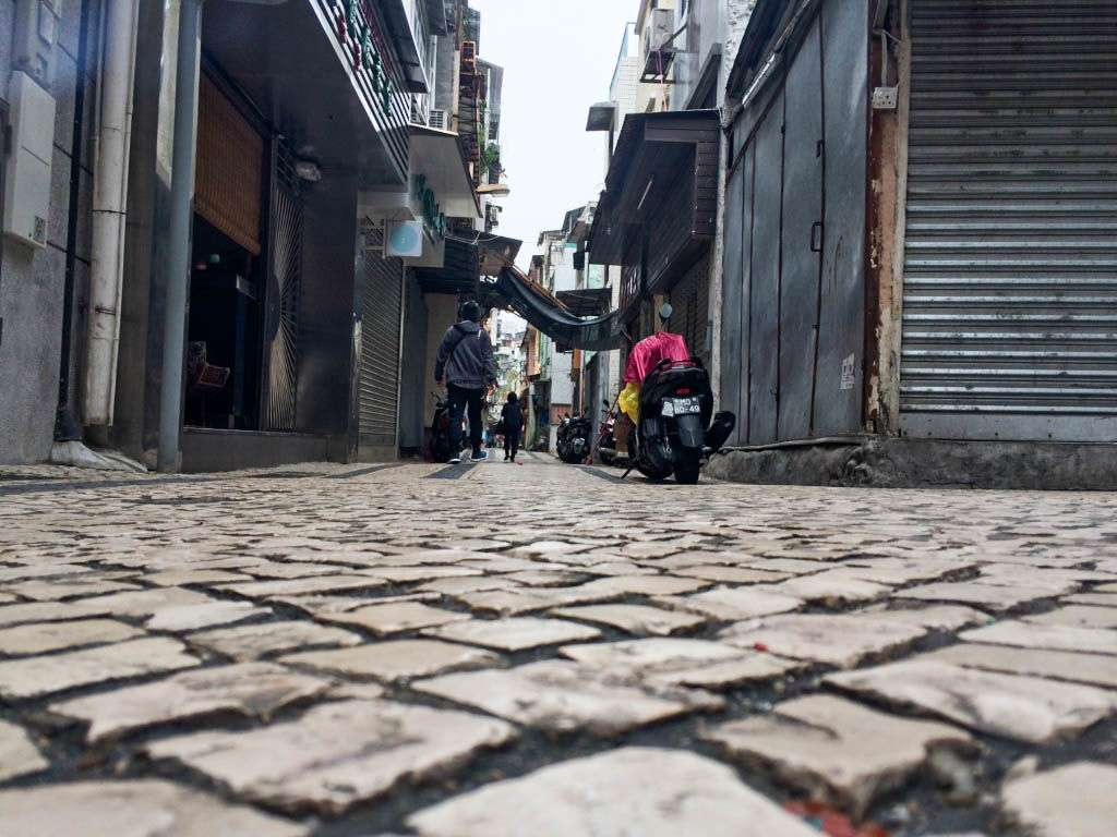 A small street in Macau with people walking.