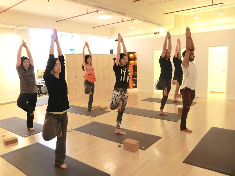 People in a yoga class doing the tree pose