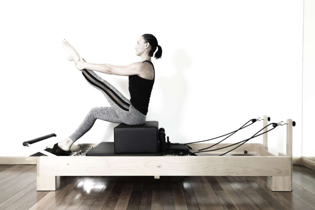 Women on pilates machine with one leg up