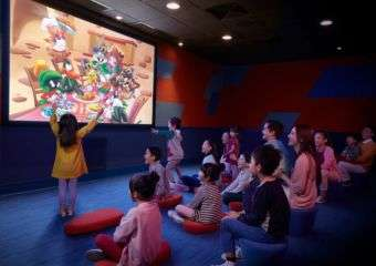 Children sitting on floor watching a cartoon movie on a big screen