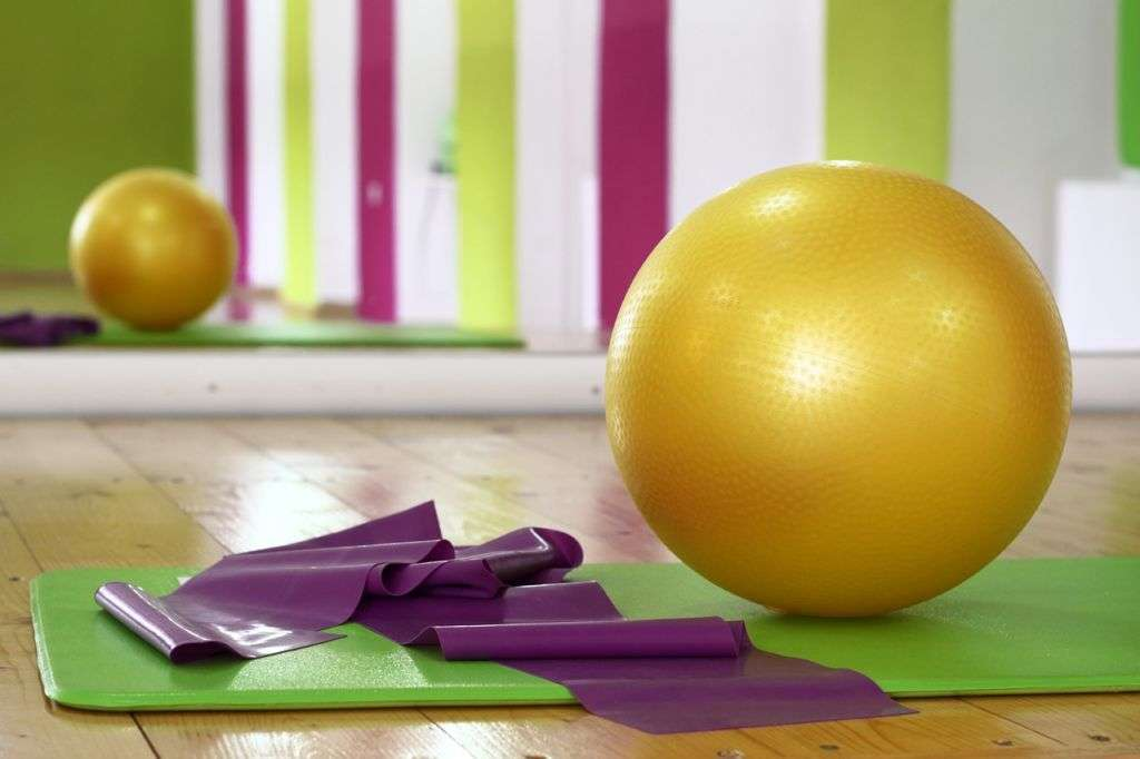 Yellow yoga ball on green mat and reflection in the mirror