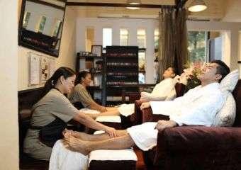 Beautician at La Belle massages a client's leg.