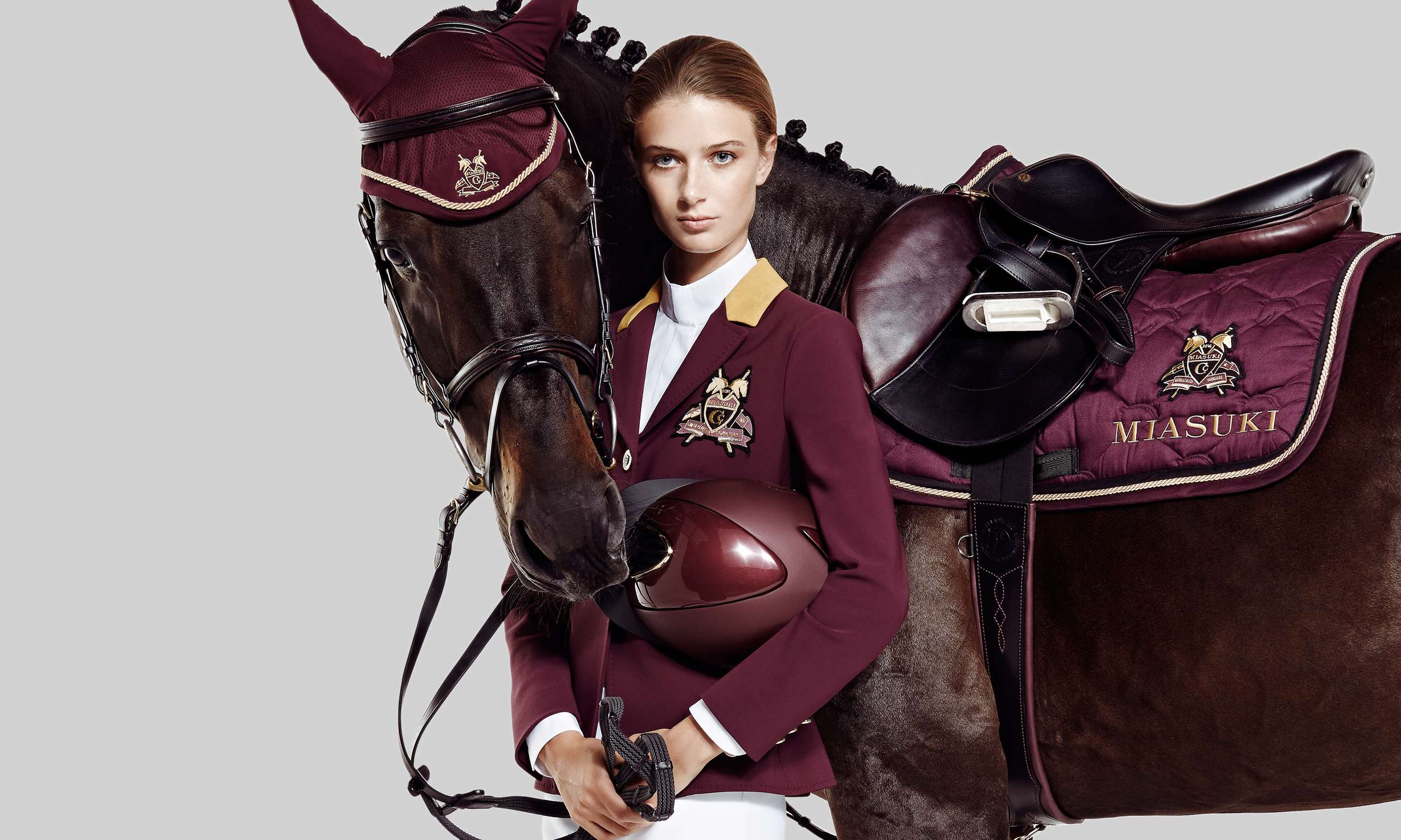 Female model in equistrian clothes and horse