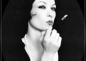 Ines Trickovic holding cigarette holder in classy black and white portrait.