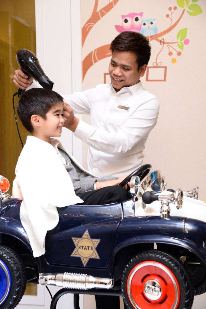 A kid gets hair blow dried by hairdresser at JW Marriot Hair Salon