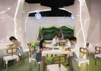 children sit at play tables at JW Marriots Kids Club in Macau