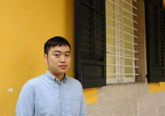 Photographer Tang Kuok Hou in Macau posing against yellow backdrop on the street.