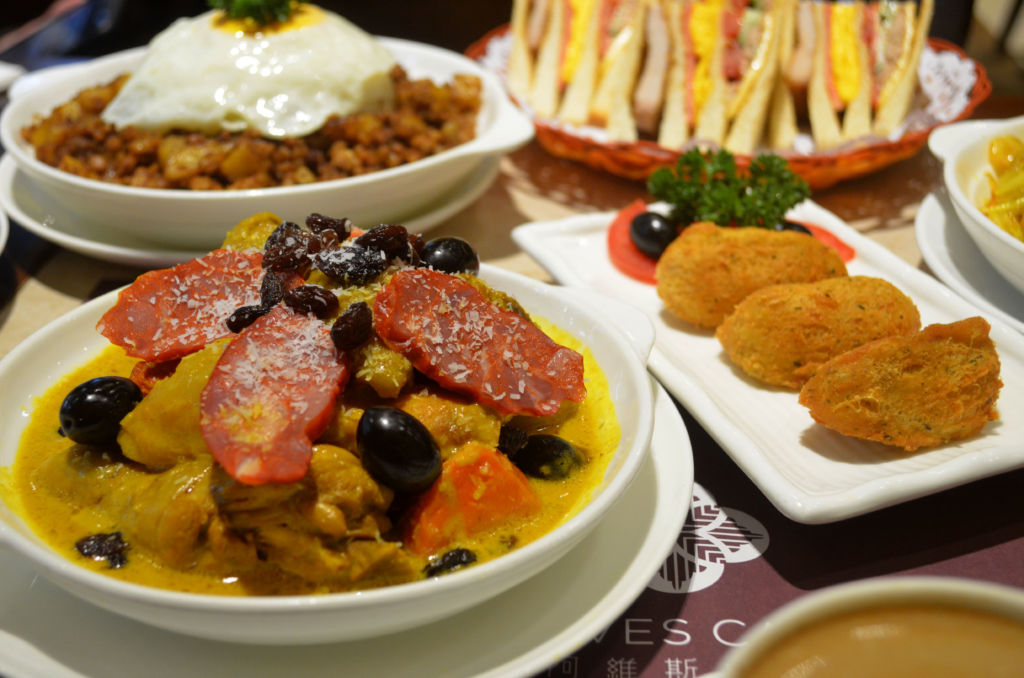 A curry dish at Alves Cafe in Macau, with other dishes in the background.