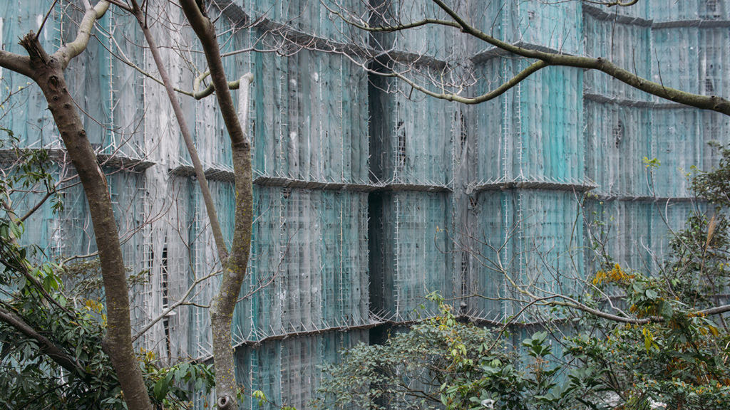 Construction netting covering building facade in photo by photographer Tang Kuok Hou in Macau.