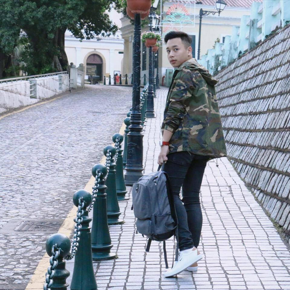 A young man wearing camouflage jacket, jeans, and white shoes walks on street in Macau.
