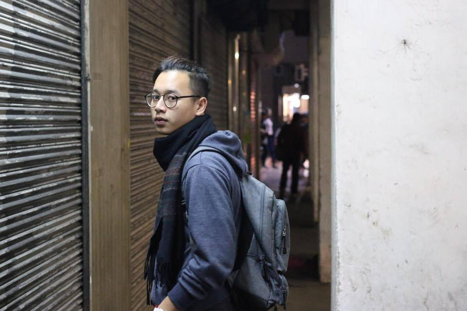 A young man wearing glasses, sweatshirt, scarf, and backpack poses in Macau alleyway at night.