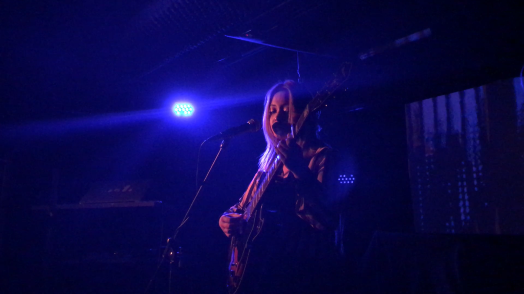 Artist Amanda Chan performing with her guitar