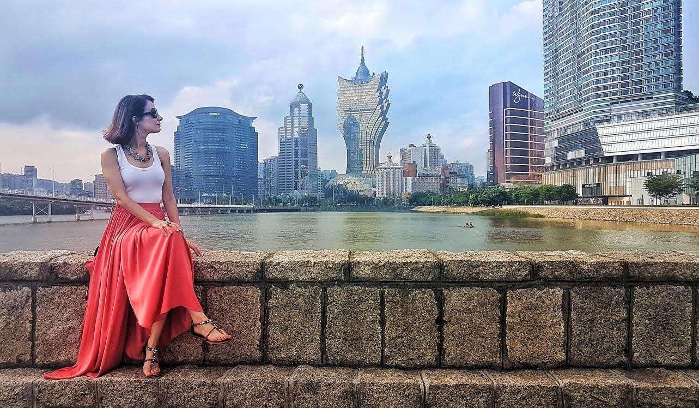 Andreia Neto posing in long red skirt against backdrop of Macau cityscape.