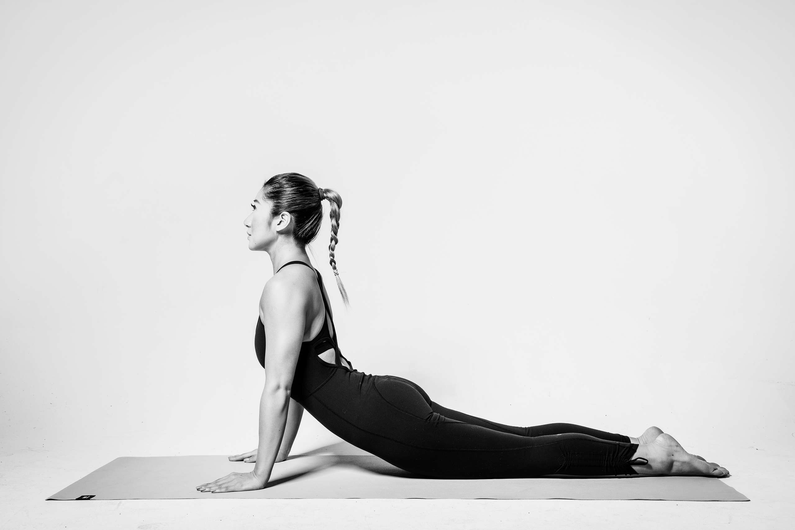Ceci Lam pilates pose on a mat black and white