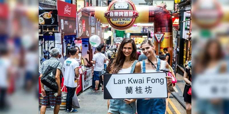 Two girls holding street sign at Lan Kwai Fong Beer and Music Fest 2017 in Hong Kong.