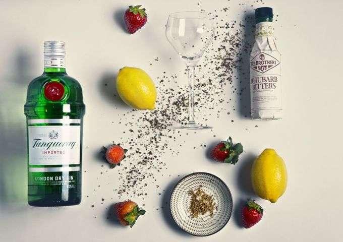 Various bar ingredients including bottle of gin, fruit, and seasonings.