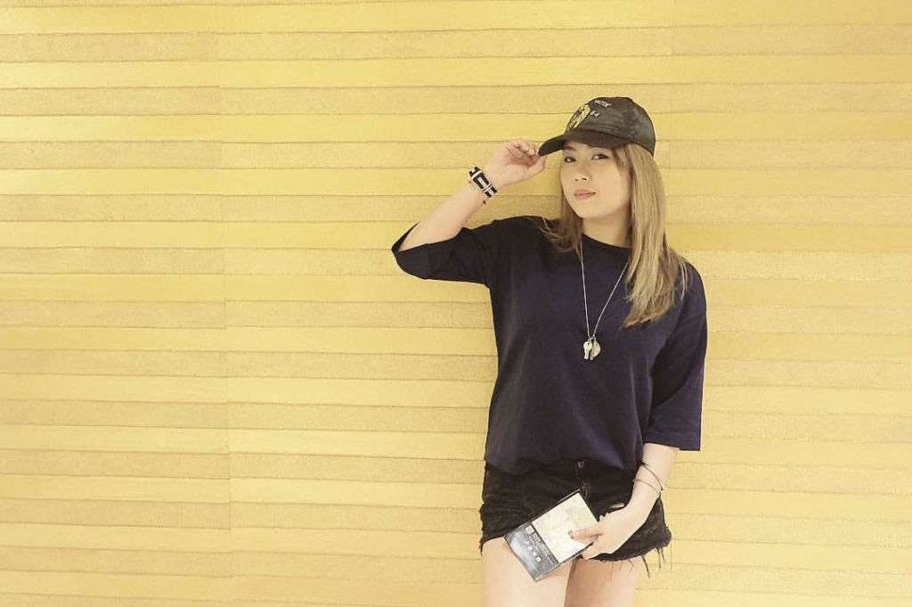 A girl poses against a yellow background wearing a black hat, black top, and shorts.