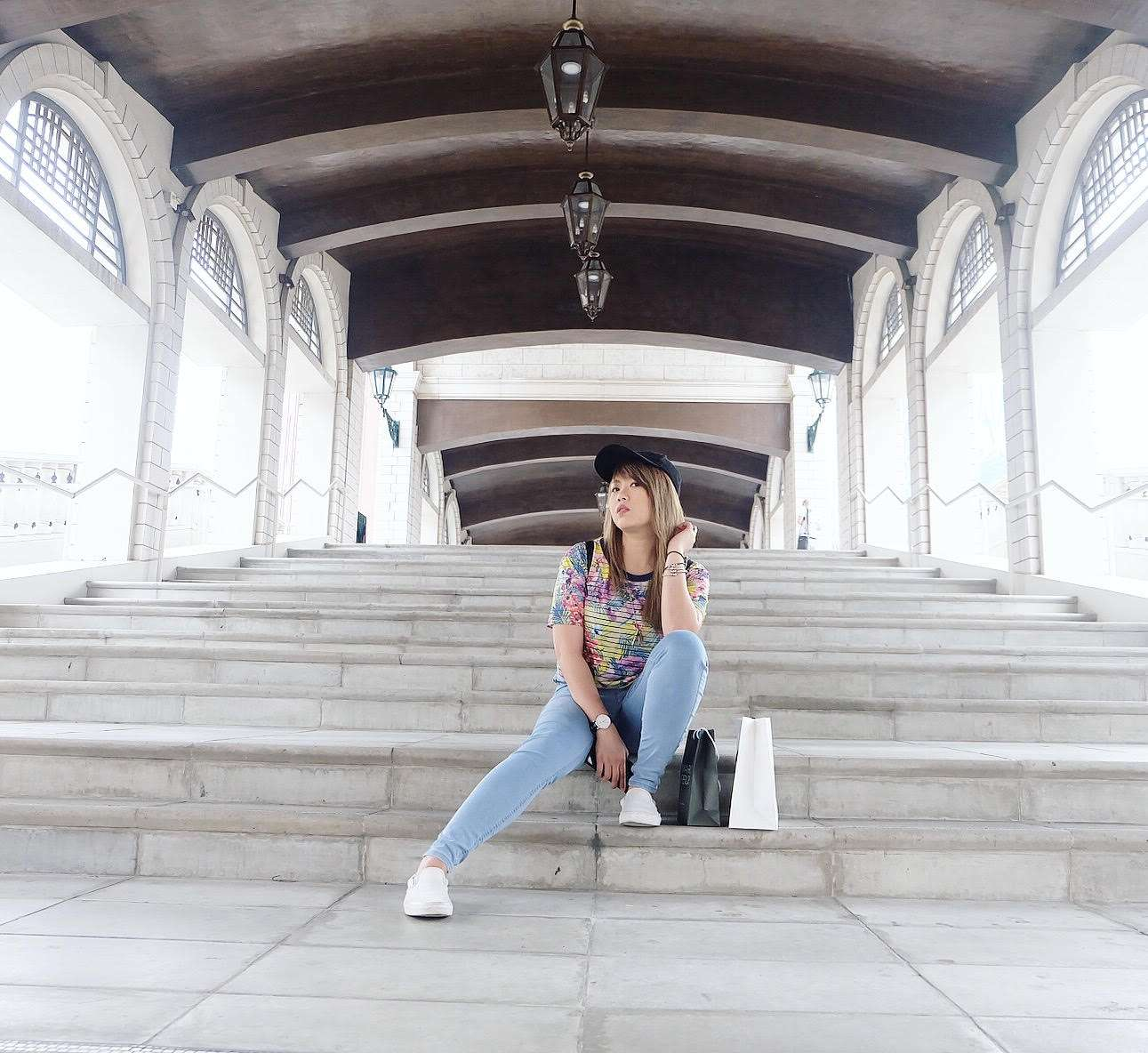 A girl poses outside in Macau on some steps, wearing a dark hat, multicolored top, jeans, and white shoes.
