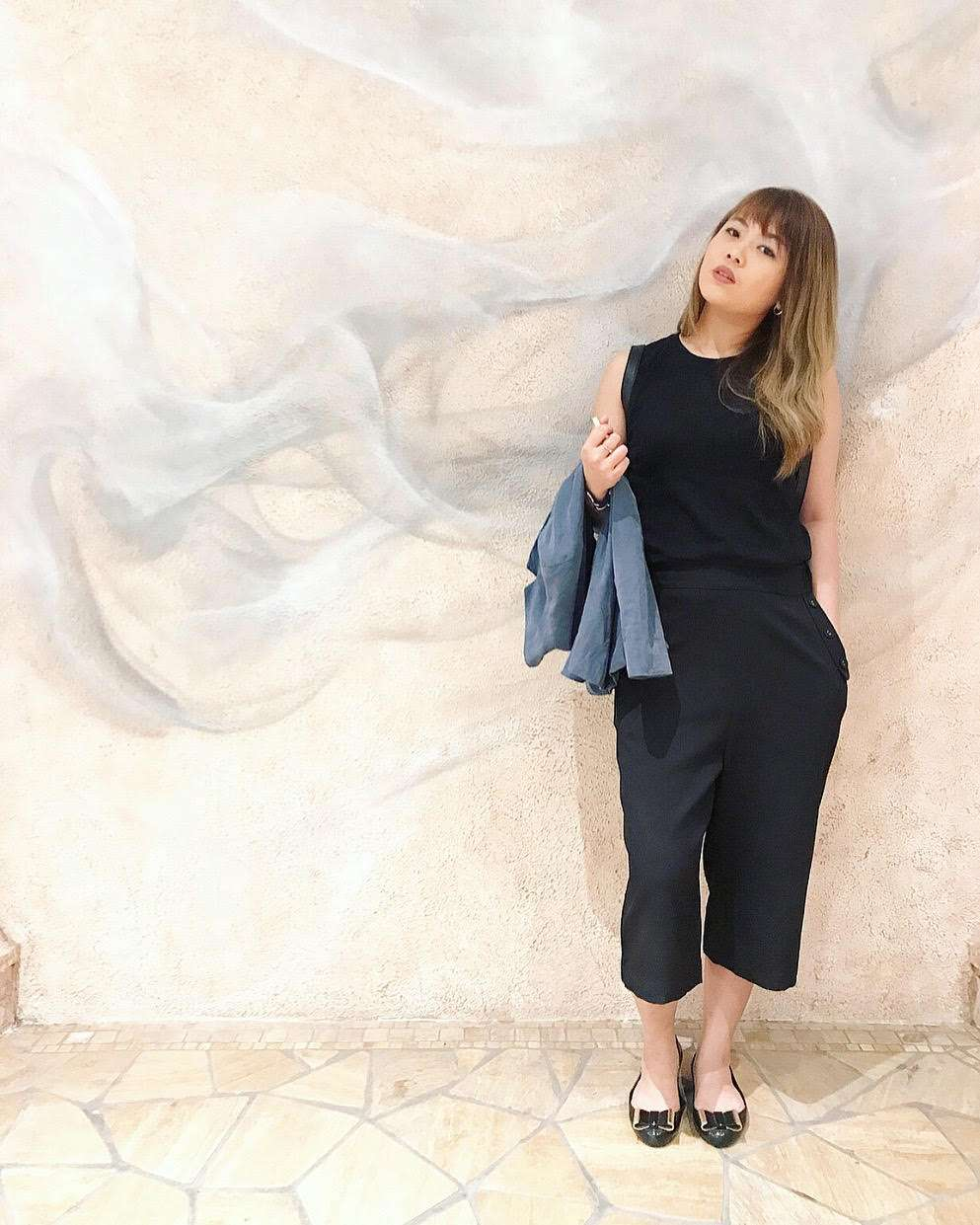 A girl in Macau poses against a wall wearing a black top and slacks.
