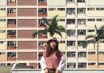 A girl wearing red top and brown skirt poses in front of apartment block in Macau.