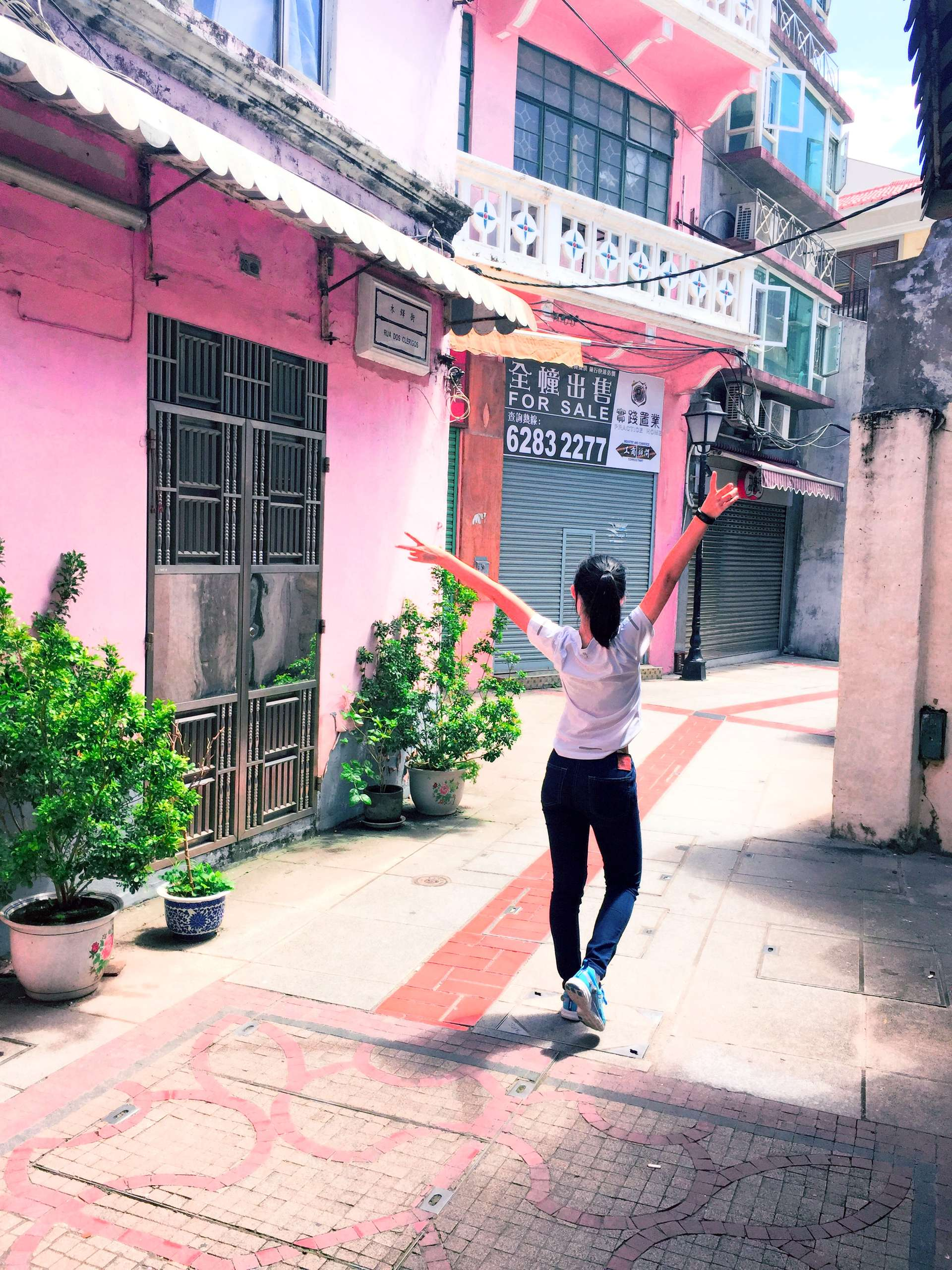 A girl in Macau walks down the street wearing a white t-shirt, dark blue jeans, and light blue shoes.