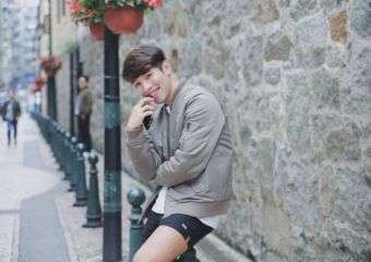 Patrick Dungo poses outside on the street in Macau, wearing a grey top and black shorts.