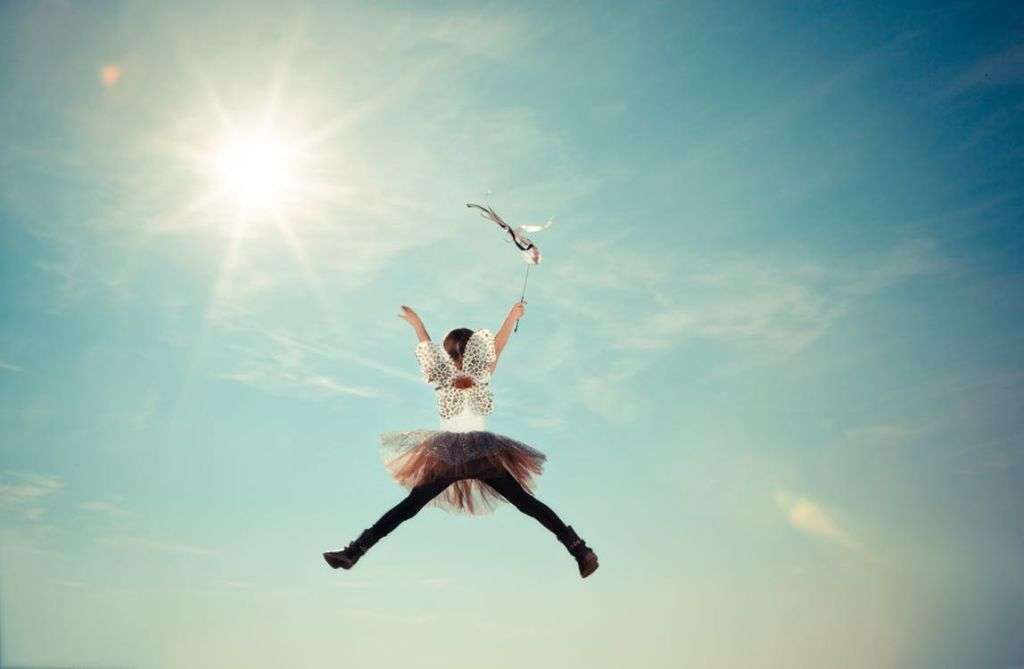 Little girl jumping in the sun with tutu and butterfly wings