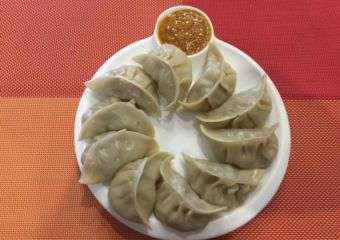 Chinese style dumplings on a plate set against red background at Gurkhas' taste Nepal restaurant in Macau