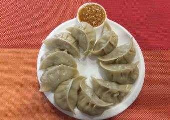 Chinese style dumplings on a plate set against red background at Gurkhas' taste Nepal restaurant in Macau