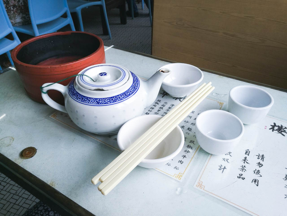 Teapot, bowls, and chopsticks on table in Long Wah teahouse in Macau.