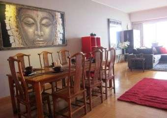 Living room with a dining table and Budda image on the wall