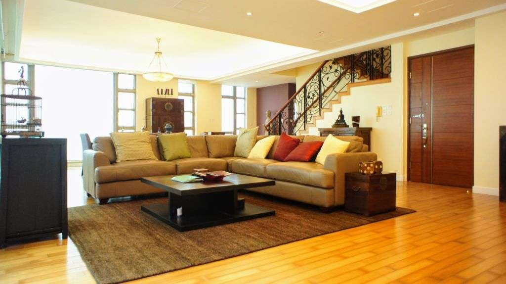 Living room with grey couch and staircase going up landlords macau