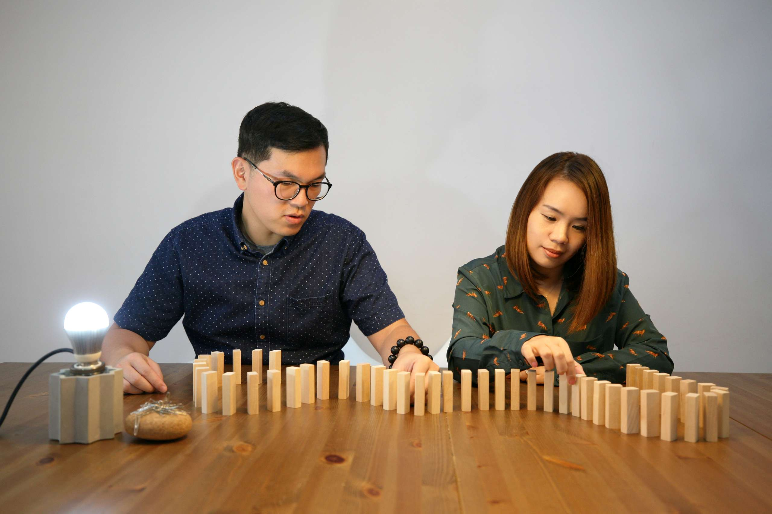 Nomad Design Macau Stanley and Sadie moving wooden blocks around a table and thinking about a design project.