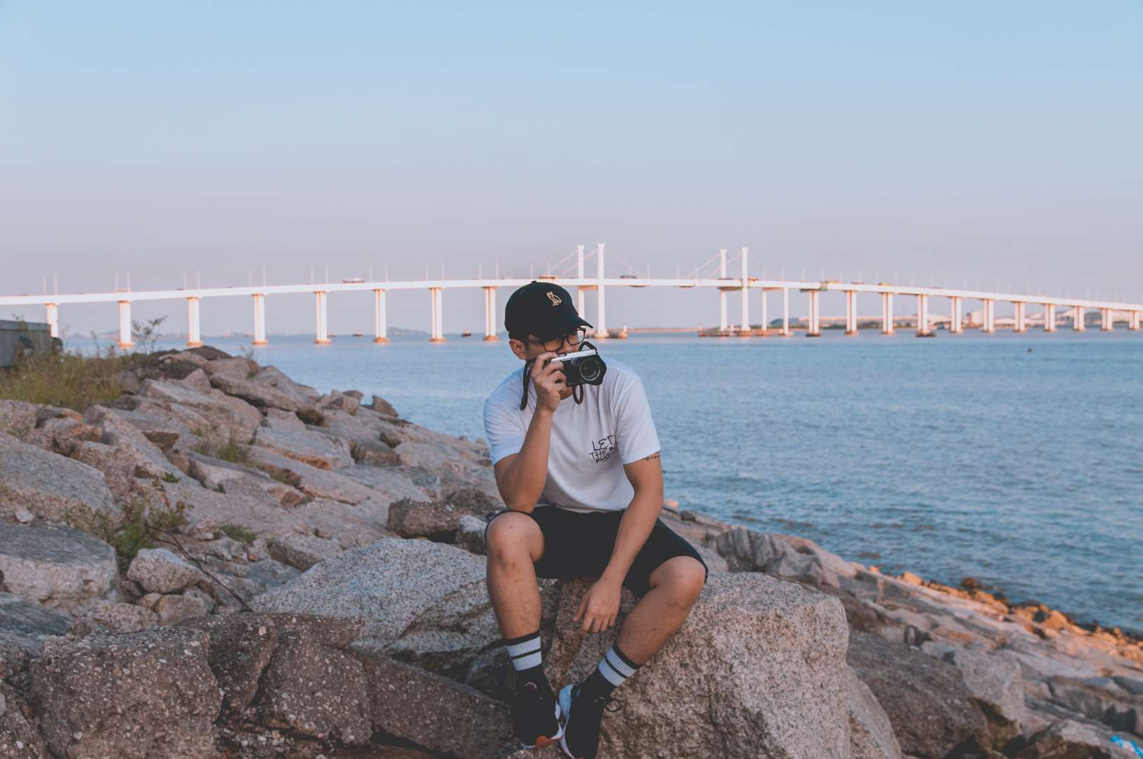 Lance Relucio sits on rocks near the water with Taipa bridge in the background.