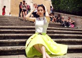A girl in Macau poses on steps wearing a white top and lime green skirt.