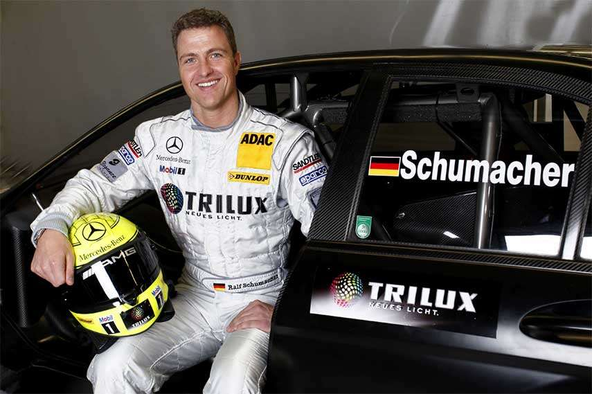 Ralf Schumacher poses sitting in a black Mercedes.