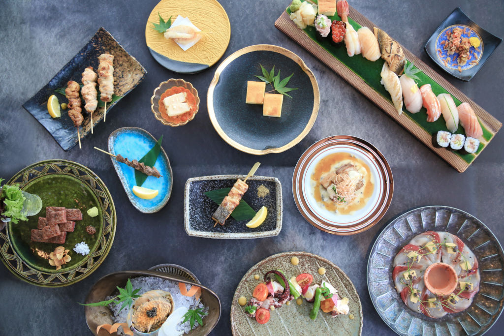 A table laid out with various sushi dishes