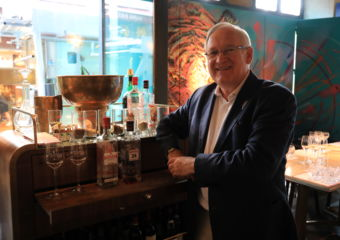 Beefeater Desmond Payne poses with some glasses of gin
