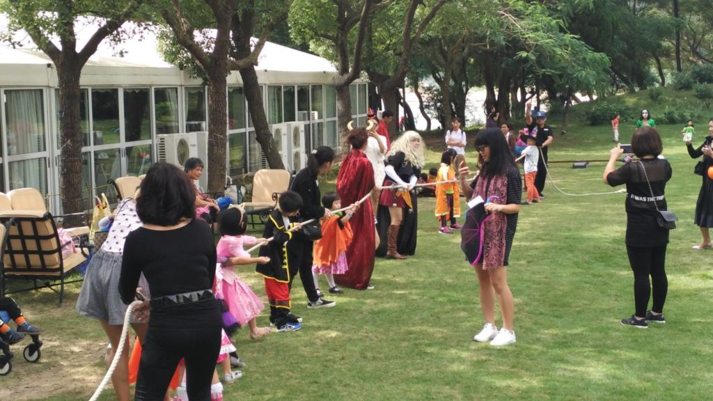 Children and adults playing Halloween party games on the lawn of the Grand Coloane Resort in Macau.