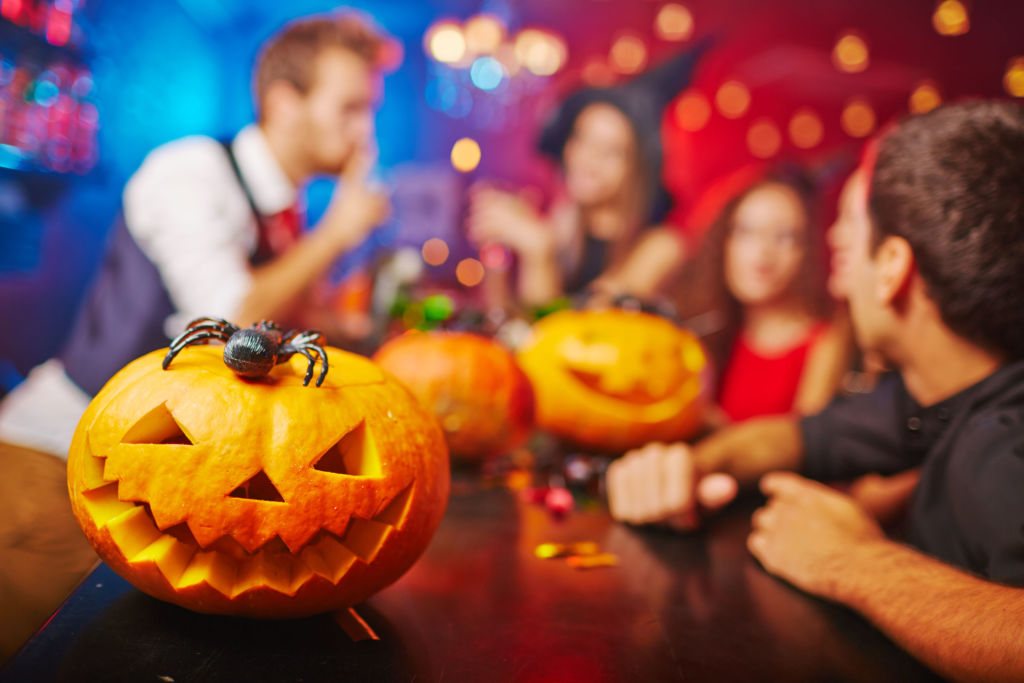 A carved pumpkin sits on a table with party going in background